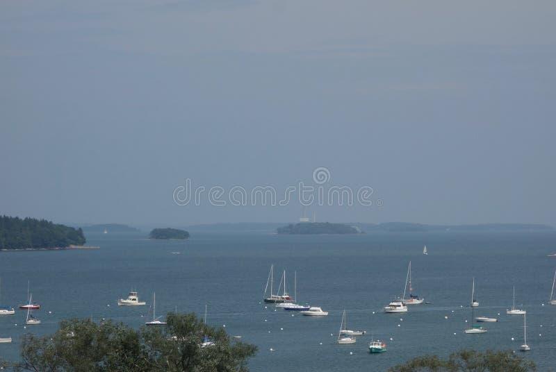Îles vertes, douzaines de bateaux blancs, l'eau bleue de baie, jour brumeux image libre de droits