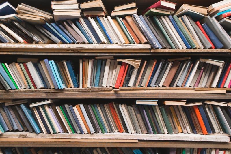 Ράφια των βιβλίων σε ένα υπόβαθρο βιβλιοθηκών Παλαιά βιβλία έξω--ο-κιβωτίων στα ράφια σε μια παλαιά άνετη βιβλιοθήκη στοκ εικόνες