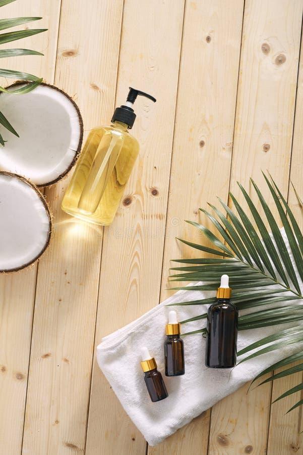 Ραγισμένη καρύδα και ένα μπουκάλι του πετρελαίου στον πίνακα - SPA, skincare, haircare και έννοια χαλάρωσης στοκ φωτογραφία με δικαίωμα ελεύθερης χρήσης