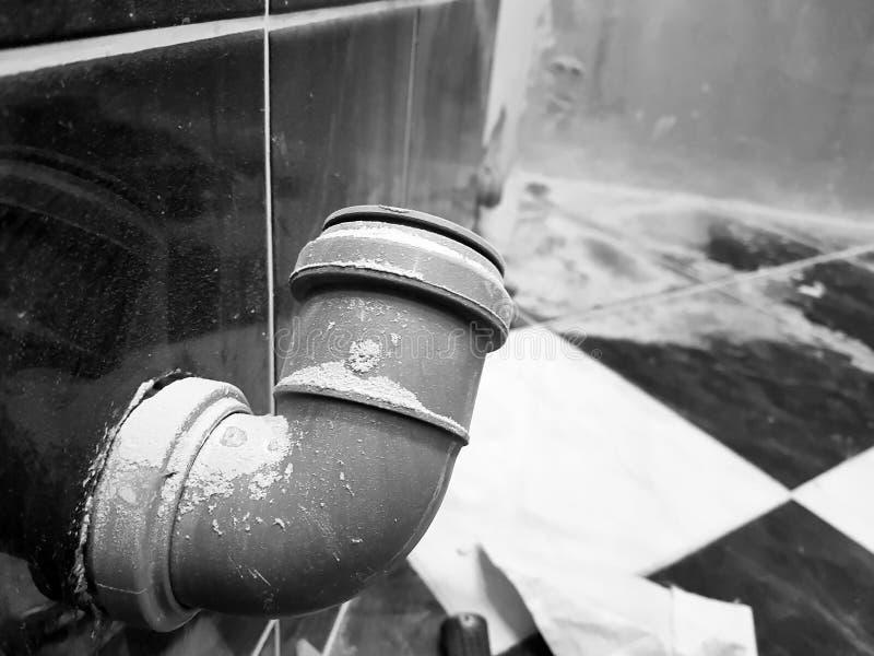 Ραμμένος σωλήνας υπονόμων σε έναν τουβλότοιχο και έναν σωλήνα προπυλενίου στοκ φωτογραφία