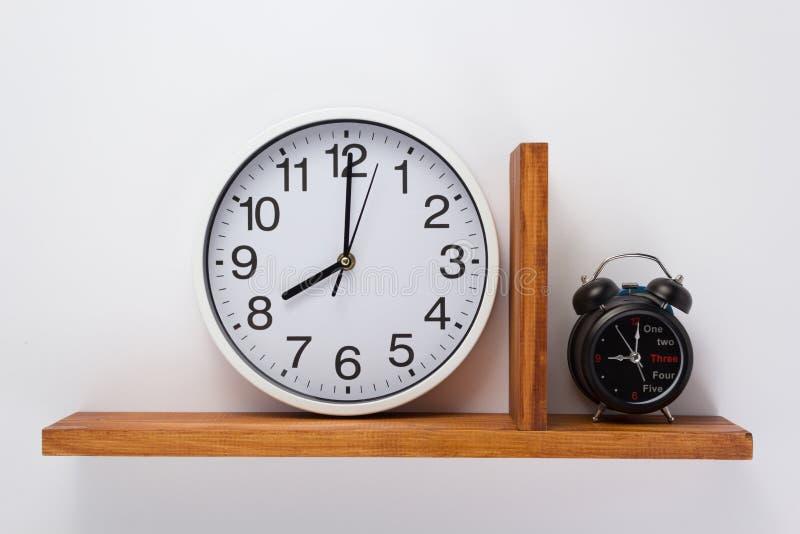 Ρολόι συναγερμών και τοίχων στο ξύλινο ράφι στοκ φωτογραφίες