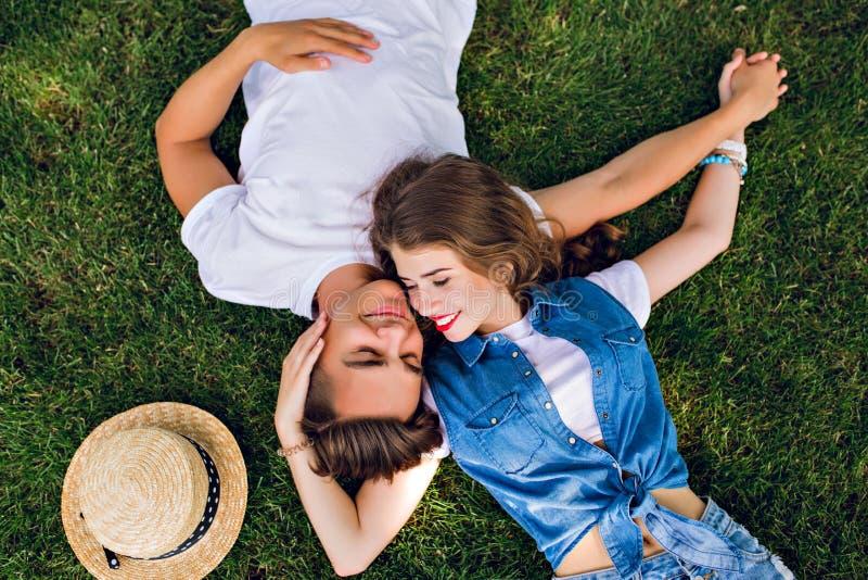 Ρομαντικό ζεύγος των νέων που βρίσκονται στη χλόη στο πάρκο Βάζουν στους ώμους μεταξύ τους και λαβής των χεριών από κοινού στοκ φωτογραφία με δικαίωμα ελεύθερης χρήσης