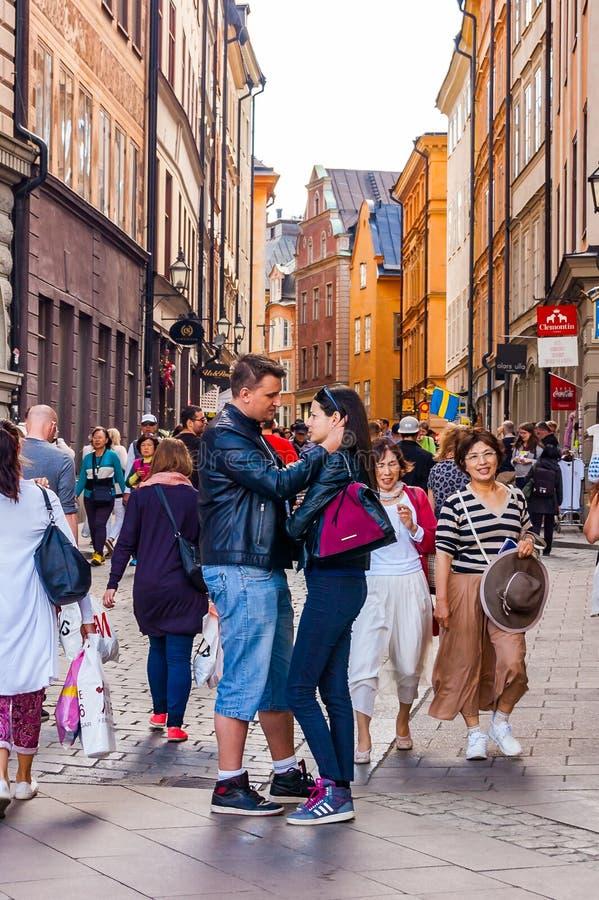 Ρομαντικό ζεύγος που στέκεται στο κέντρο της συσσωρευμένης μεσαιωνικής οδού σε Gamla Stan, παλαιά πόλη της Στοκχόλμης στοκ φωτογραφία