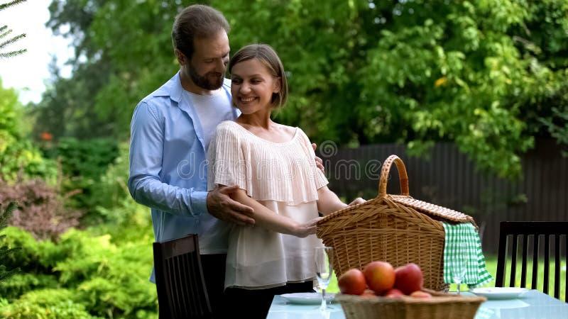 Ρομαντικό πικ-νίκ στο εξοχικό σπίτι, σύζυγος που αγκαλιάζει τη σύζυγο, ευτυχής τρυφερή οικογένεια στοκ εικόνες με δικαίωμα ελεύθερης χρήσης