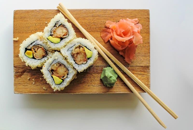 Ρόλοι maki σουσιών με τους σπόρους και το αβοκάντο σουσαμιού, με chopsticks, το wasabi και την πιπερόριζα - κλείστε επάνω την άπο στοκ φωτογραφία με δικαίωμα ελεύθερης χρήσης