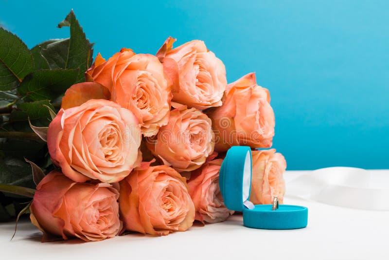Ρόδινα τριαντάφυλλα και δαχτυλίδι εκμετάλλευσης κιβωτίων γαμήλιο στο μπλε υπόβαθρο στοκ εικόνες με δικαίωμα ελεύθερης χρήσης
