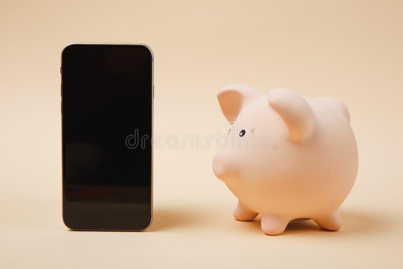 Ρόδινη piggy τράπεζα χρημάτων πλάγιας όψης, κινητό τηλέφωνο με την κενή κενή οθόνη στο μπεζ υπόβαθρο τοίχων Χρήματα στοκ εικόνες