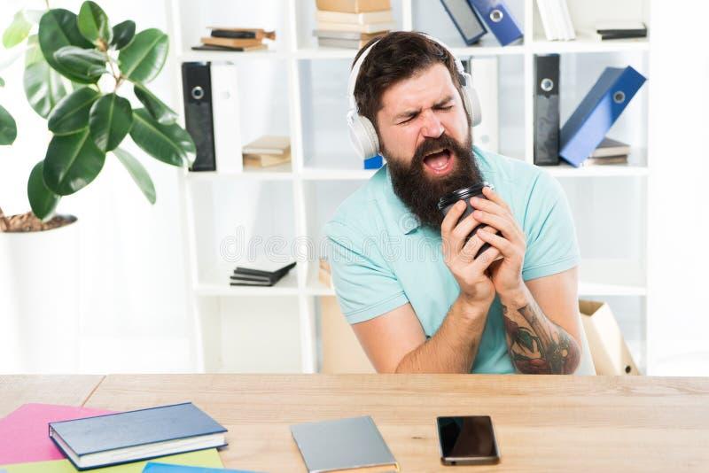 Ρυθμός ζωής γραφείων Κανονική ημέρα γραφείων Τα γενειοφόρα ακουστικά τύπων ατόμων κάθονται το γραφείο ακούνε μουσική τραγουδούν τ στοκ εικόνες με δικαίωμα ελεύθερης χρήσης