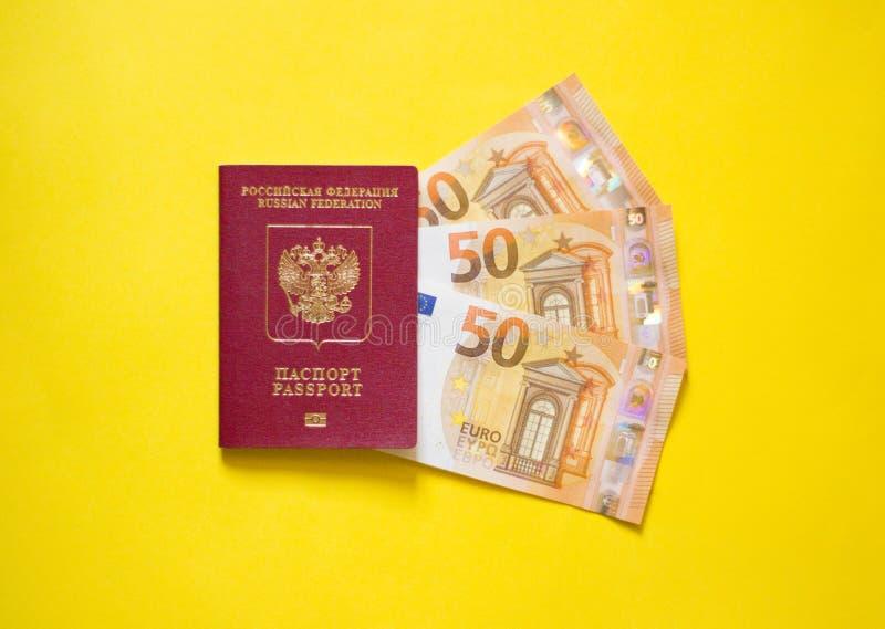 Ρωσικό διαβατήριο με το ευρώ στο κίτρινο υπόβαθρο στοκ φωτογραφίες με δικαίωμα ελεύθερης χρήσης