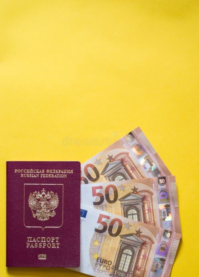 Ρωσικό διαβατήριο με το ευρώ στο κίτρινο υπόβαθρο στοκ εικόνα