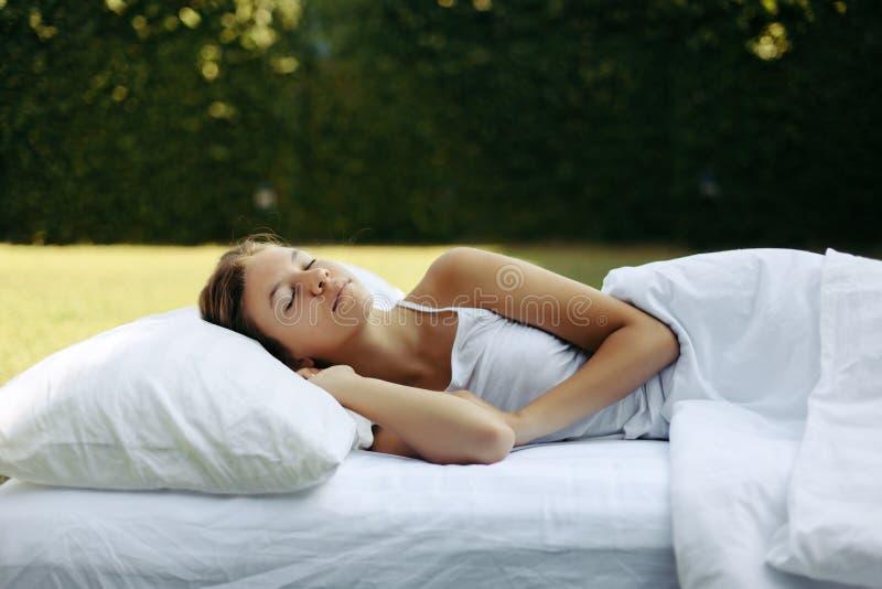 Ύπνος κοριτσιών στα matress στη χλόη στοκ φωτογραφία