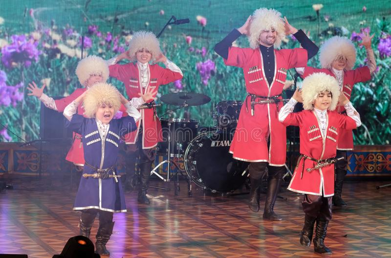 2019-03-06,库斯塔奈,哈萨克斯坦 Lezginka 男孩在阶段跳舞小组执行与一个民间白种人男性舞蹈 免版税库存图片