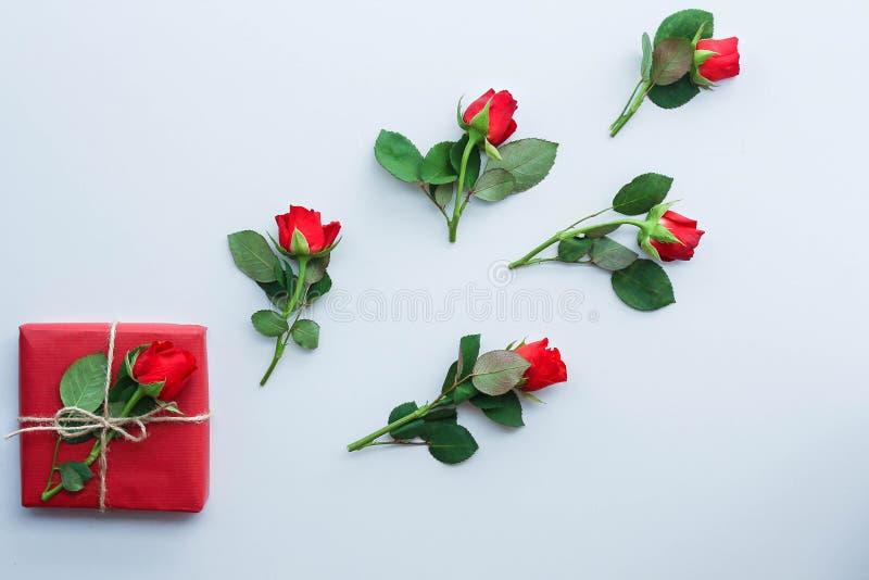 Όμορφα τριαντάφυλλα και κιβώτιο δώρων στο ελαφρύ υπόβαθρο στοκ εικόνες με δικαίωμα ελεύθερης χρήσης