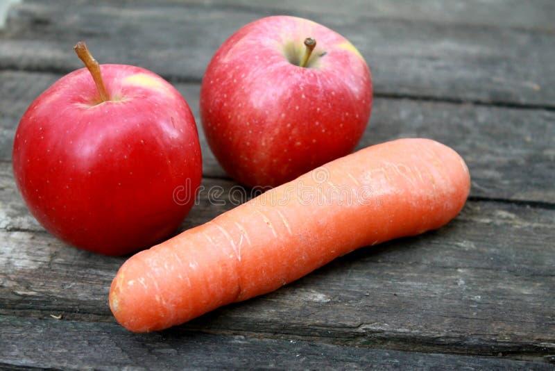 Όμορφα φρέσκα juicy ώριμα πορτοκαλιά καρότα και δύο κόκκινα μήλα βάζουν στον πίνακα στοκ φωτογραφίες