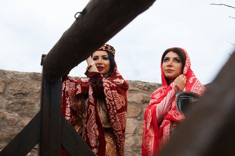Όμορφες Μεσο-Ανατολικές γυναίκες που φορούν το παραδοσιακό φόρεμα, που θέτει υπαίθρια στοκ φωτογραφίες