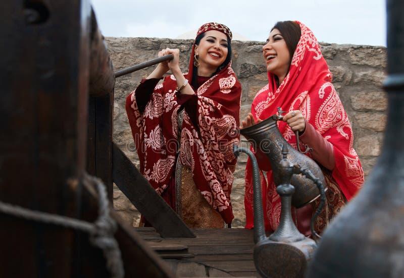 Όμορφες Μεσο-Ανατολικές γυναίκες που φορούν το παραδοσιακό φόρεμα, που θέτει υπαίθρια στοκ εικόνες