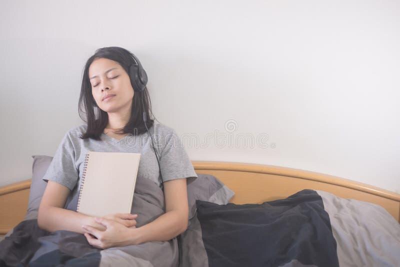 Όμορφη ασιατική μουσική ακούσματος γυναικών με το ακουστικό και ανάγνωση της χαλάρωσης βιβλίων στο κρεβάτι στοκ φωτογραφία με δικαίωμα ελεύθερης χρήσης