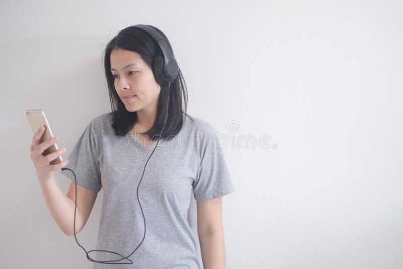 Όμορφη ασιατική μουσική ακούσματος γυναικών με το ακουστικό και το smartphone σε ένα άσπρο υπόβαθρο με το διάστημα αντιγράφων στοκ εικόνες με δικαίωμα ελεύθερης χρήσης
