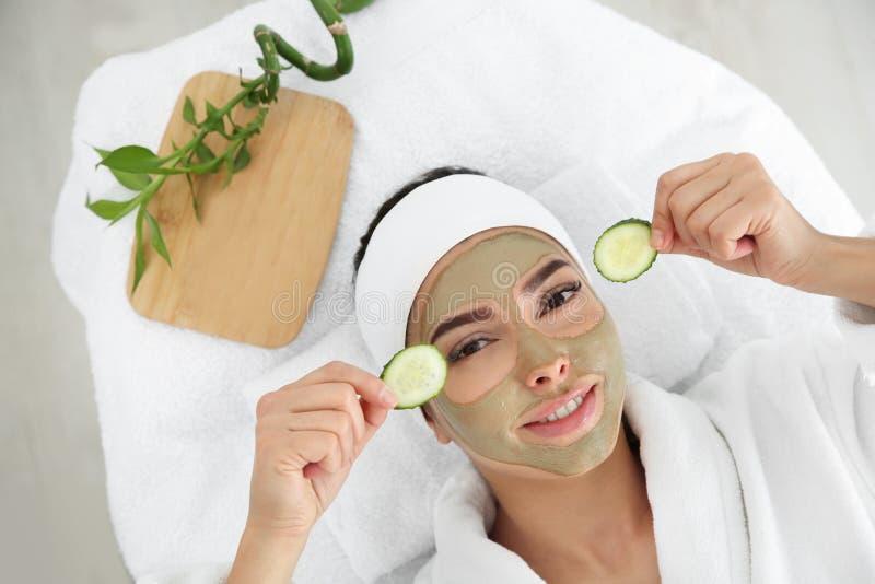 Όμορφη γυναίκα με τη μάσκα αργίλου στις φέτες αγγουριών εκμετάλλευσης προσώπου της στο σαλόνι SPA στοκ εικόνες