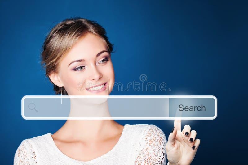Όμορφη γυναίκα με τον κενό φραγμό διευθύνσεων με το εικονίδιο αναζήτησης στην εικονική μηχανή αναζήτησης Ιστού στο μπλε υπόβαθρο στοκ εικόνες
