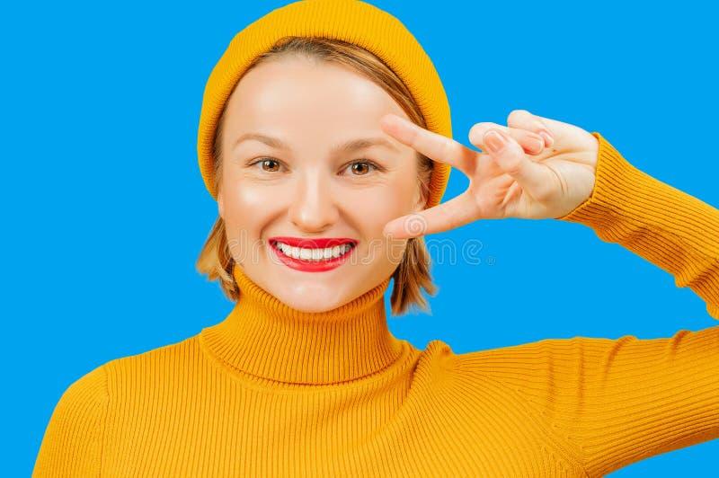 Όμορφη γυναίκα στο μπλε υπόβαθρο που χαμογελά με το ευτυχές πρόσωπο που κάνει το σημάδι νίκης στοκ εικόνα