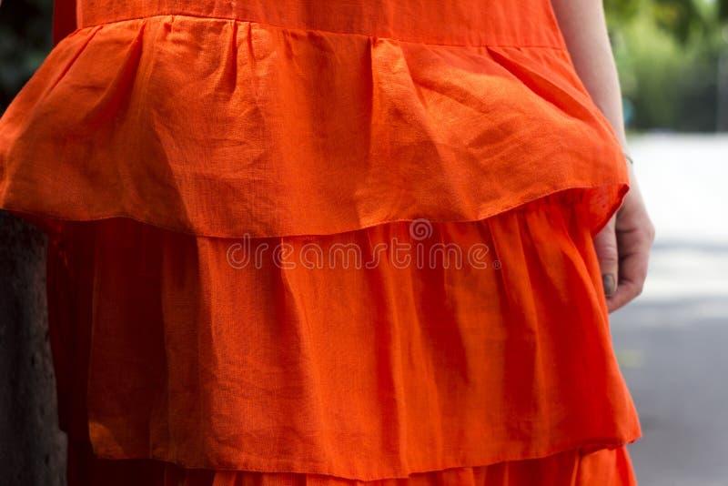 Όμορφη γυναίκα στο πορτοκαλί φόρεμα λινού με ruffles, θερινό ύφος, μόδα Ο χαμηλότερος - το μισό από το φόρεμα, κινηματογράφηση σε στοκ φωτογραφία