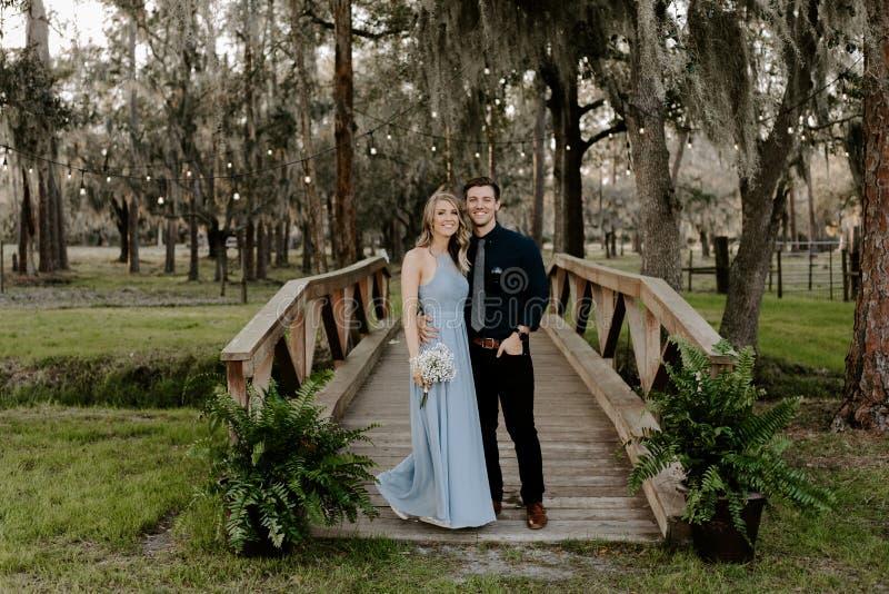 Όμορφη γυναίκα παράνυμφων στο μπλε φόρεμα και ανθοδέσμη με την ημερομηνία της σε ένα επίσημο γεγονός εορτασμού δεξίωσης γάμου έξω στοκ εικόνες