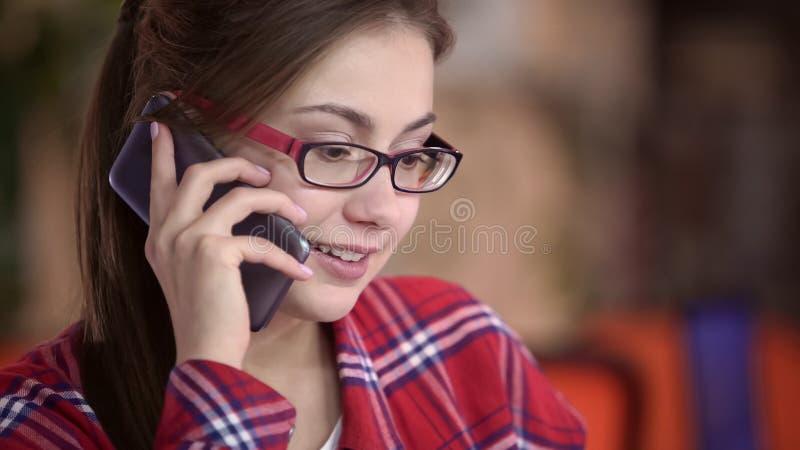 Όμορφη γυναίκα eyeglasses που μιλούν στο smartphone, την επικοινωνία και τη συσκευή στοκ εικόνα