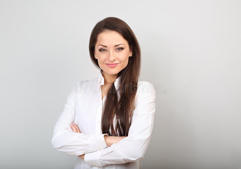 Όμορφη επιχειρησιακή ήρεμη βέβαια γυναίκα στο άσπρο πουκάμισο που κοιτάζει με τα διπλωμένα όπλα στο μπλε υπόβαθρο χρώματος στοκ φωτογραφία με δικαίωμα ελεύθερης χρήσης