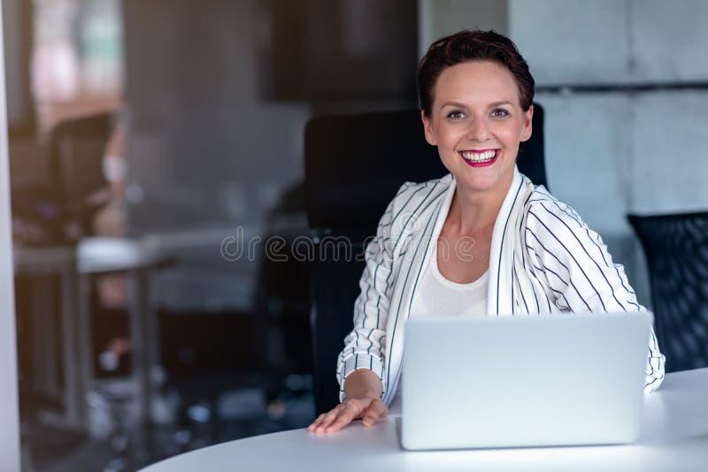 Όμορφη επιχειρησιακή κυρία με το φορητό προσωπικό υπολογιστή στην αρχή στοκ εικόνες