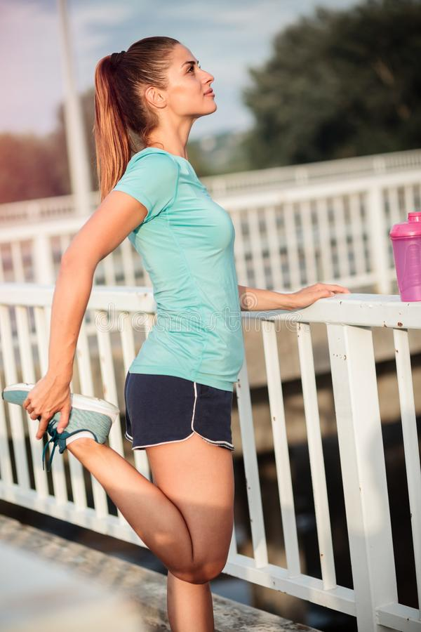 Όμορφη ικανοποιημένη νέα γυναίκα που τεντώνει και που στηρίζεται μετά από ένα σκληρό workout στοκ φωτογραφίες