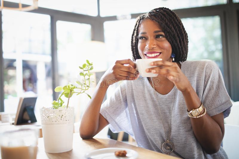 Όμορφη νέα αφρικανική γυναίκα που απολαμβάνει ένα φλιτζάνι του καφέ χαλαρώνοντας στη καφετερία στοκ εικόνες