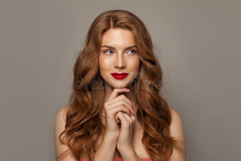 Όμορφη νέα κοκκινομάλλης γυναίκα με τη μακριά σγουρή τρίχα ομορφιάς στο καφετί υπόβαθρο στοκ φωτογραφία με δικαίωμα ελεύθερης χρήσης
