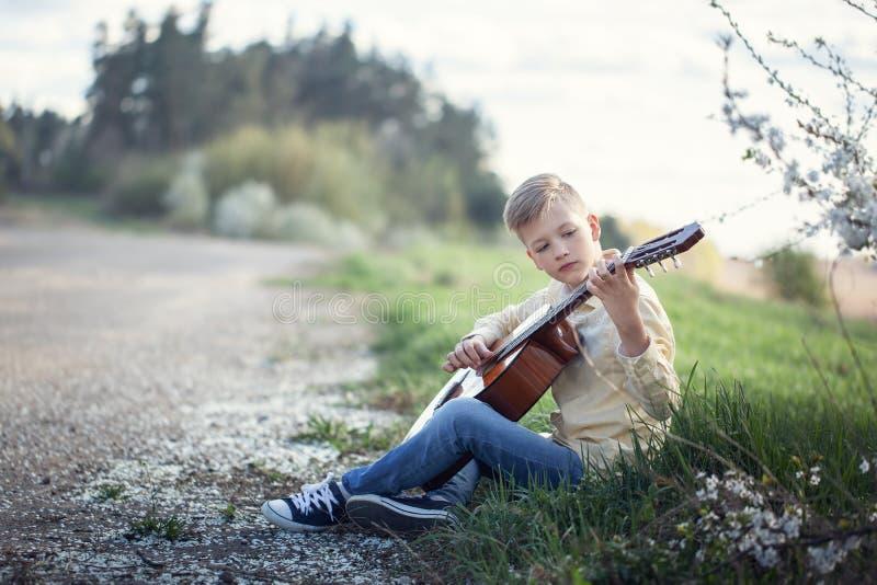 Όμορφος έφηβος με τη συνεδρίαση κιθάρων στη χλόη στο πάρκο στοκ φωτογραφία