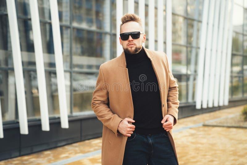 Όμορφος γενειοφόρος νεαρός άνδρας στα γυαλιά ηλίου κοντά στο εμπορικό κέντρο στοκ φωτογραφία με δικαίωμα ελεύθερης χρήσης