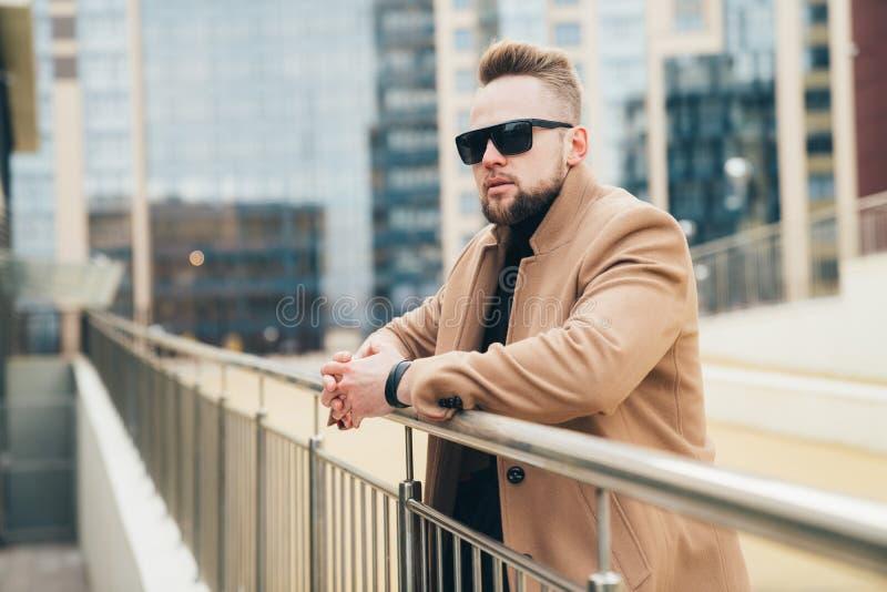 Όμορφος γενειοφόρος νεαρός άνδρας στα γυαλιά ηλίου κοντά στο εμπορικό κέντρο στοκ εικόνα