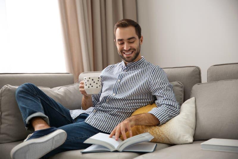 Όμορφος νεαρός άνδρας με το βιβλίο ανάγνωσης φλιτζανιών του καφέ στοκ φωτογραφίες με δικαίωμα ελεύθερης χρήσης