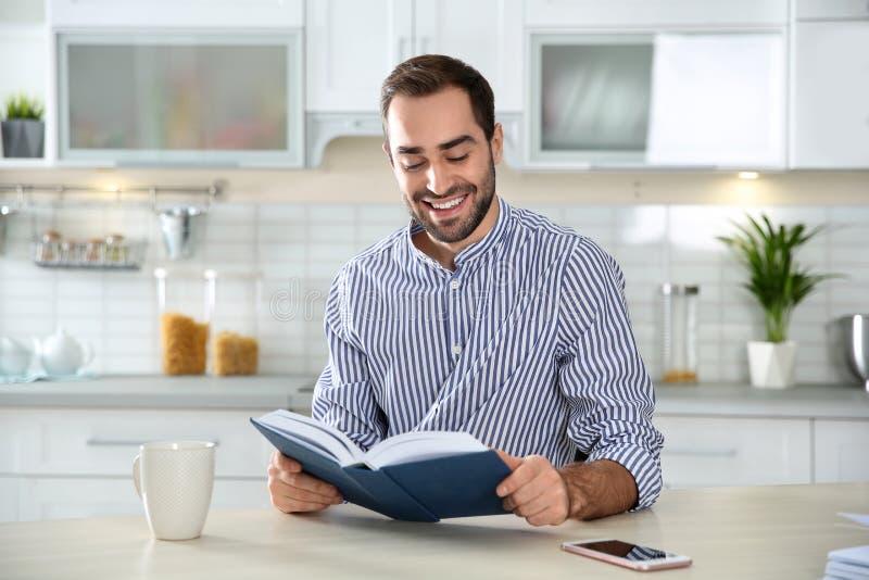 Όμορφος νεαρός άνδρας με το βιβλίο ανάγνωσης φλιτζανιών του καφέ στοκ φωτογραφία