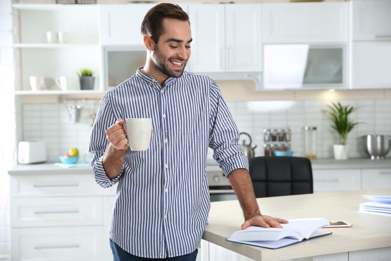 Όμορφος νεαρός άνδρας με το βιβλίο ανάγνωσης φλιτζανιών του καφέ στοκ φωτογραφίες