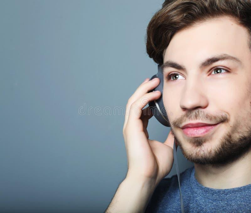 Όμορφος νεαρός άνδρας που φορά τα ακουστικά και που ακούει τη μουσική στοκ φωτογραφίες με δικαίωμα ελεύθερης χρήσης