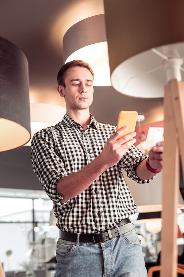 Όμορφος συγκεντρωμένος πελάτης που παίρνει την εικόνα της τιμής στο κατάστημα φωτισμού στοκ φωτογραφίες