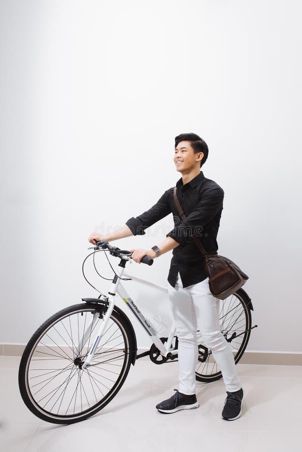 Όμορφος τύπος που υπερασπίζεται το ποδήλατο που απομονώνεται στο λευκό στοκ φωτογραφία με δικαίωμα ελεύθερης χρήσης