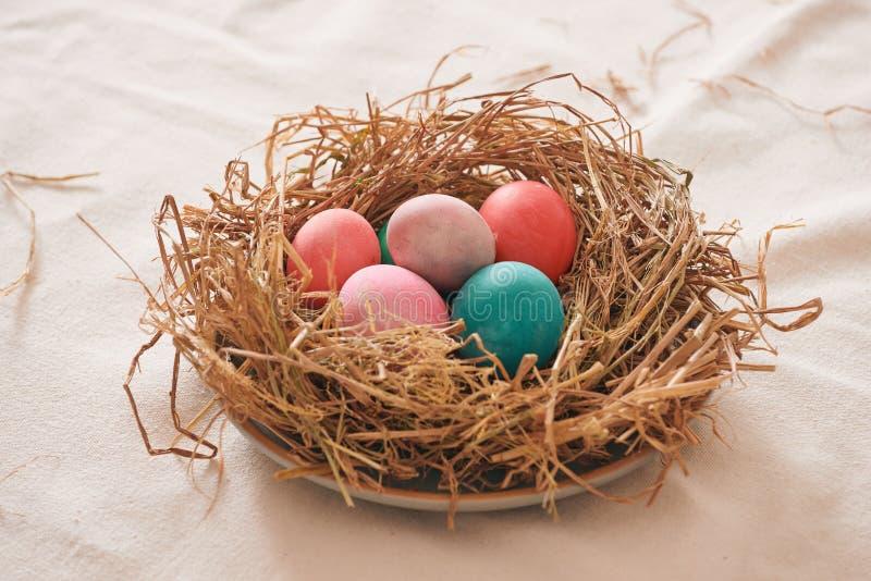 Όμορφο αυγό χρώματος Πάσχας πολυ στο άχυρο στο ξύλινο υπόβαθρο, έννοια ημέρας Πάσχας στοκ εικόνα