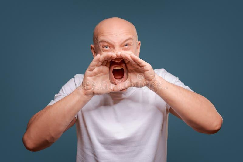 Όμορφο ευτυχές άτομο που φορά την άσπρη μπλούζα, τύπος που μιλά δυνατά, που απομονώνεται στο μπλε υπόβαθρο στοκ εικόνες