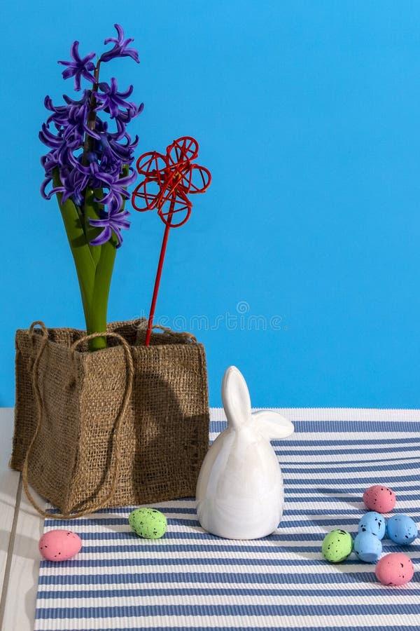 Όμορφο ευτυχές Πάσχα για το διακοσμητικό σχέδιο Ζωηρόχρωμα αυγά, λαγουδάκι και λουλούδια στο μπλε υπόβαθρο διάστημα αντιγράφων στοκ φωτογραφία με δικαίωμα ελεύθερης χρήσης