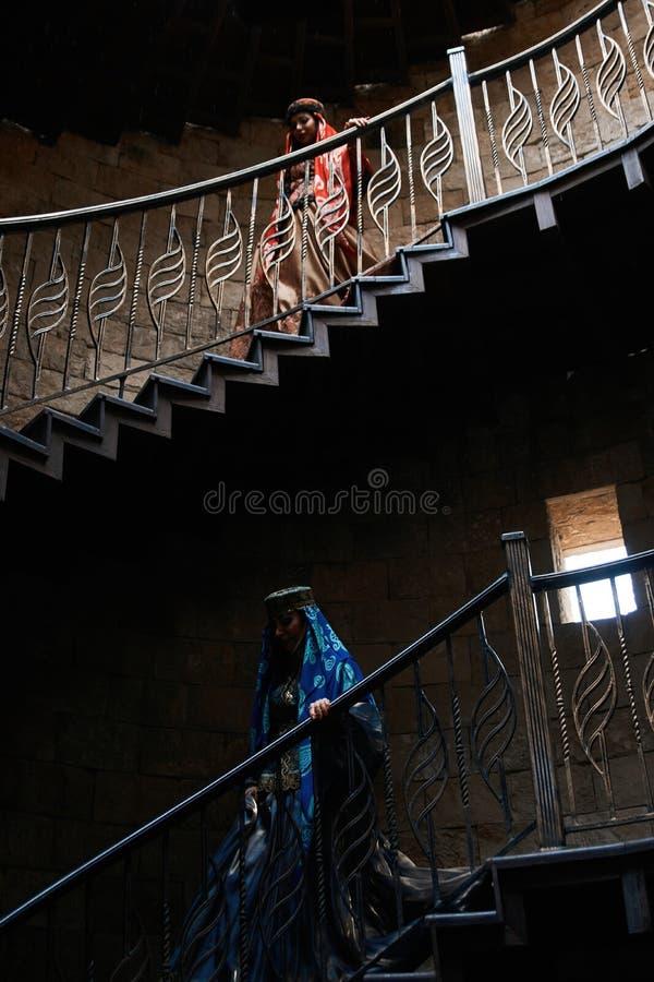 Όμορφο θηλυκό στα μοντέρνα ασιατικά ενδύματα που πηγαίνουν κάτω από τα σκαλοπάτια στοκ φωτογραφία