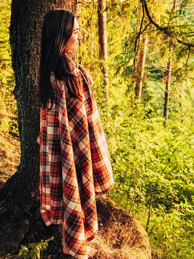Όμορφο καυκάσιο κορίτσι brunette που τυλίγεται σε ένα ελεγμένο καρό στο δάσος στο ηλιοβασίλεμα που στέκεται κοντά σε ένα δέντρο 2 στοκ εικόνα