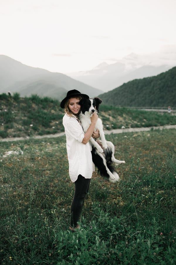 Όμορφο κορίτσι και γραπτό κόλλεϊ συνόρων σκυλιών σε ετοιμότητα της βουνό στον τομέα στοκ εικόνες