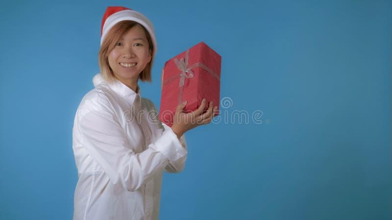 Όμορφο κορίτσι όπως το santa που κρατά το κόκκινο κιβώτιο με το παρόν στοκ φωτογραφία