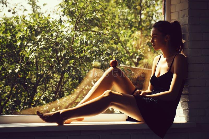 Όμορφο κορίτσι στη στρωματοειδή φλέβα παραθύρων στοκ φωτογραφία